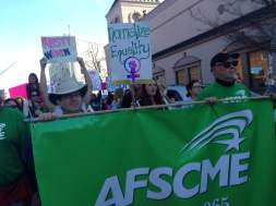AFSCME members Ben Pollock (left) and Ted Swedenburg parade the Local 965 banner Jan. 20 at the Fayetteville Women's March 2018. Member Steve boss's shoulder is at far left.