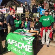 Mike Pierce (from left), Ted Swedenburg, Kelly Hammond, Bret Schulte and Steve Boss manage the Local 965 information table at the Fayetteville Women's March 2018, at the downtown square.