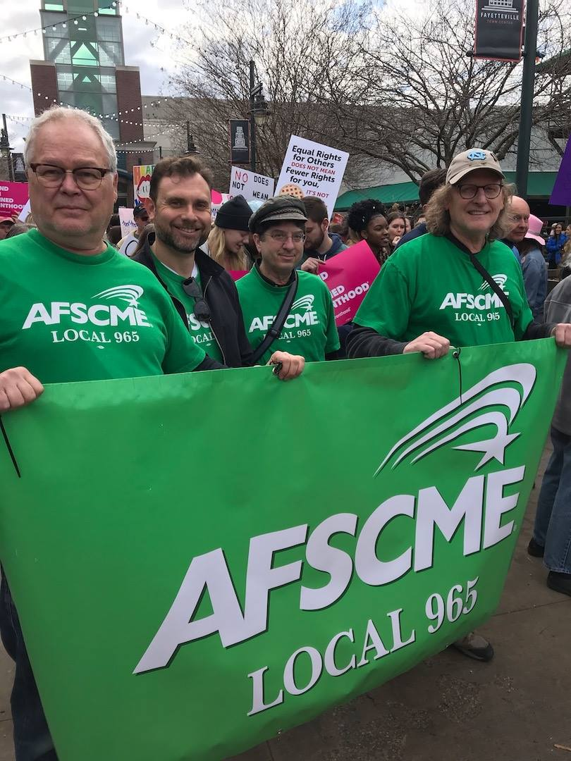 From left, Ted Swedenburg, Bret Schulte, Ben Pollock and Steve Boss hoist the Local 965 banner Feb. 2 at the 2019 NWA Women's March in downtown Fayetteville.