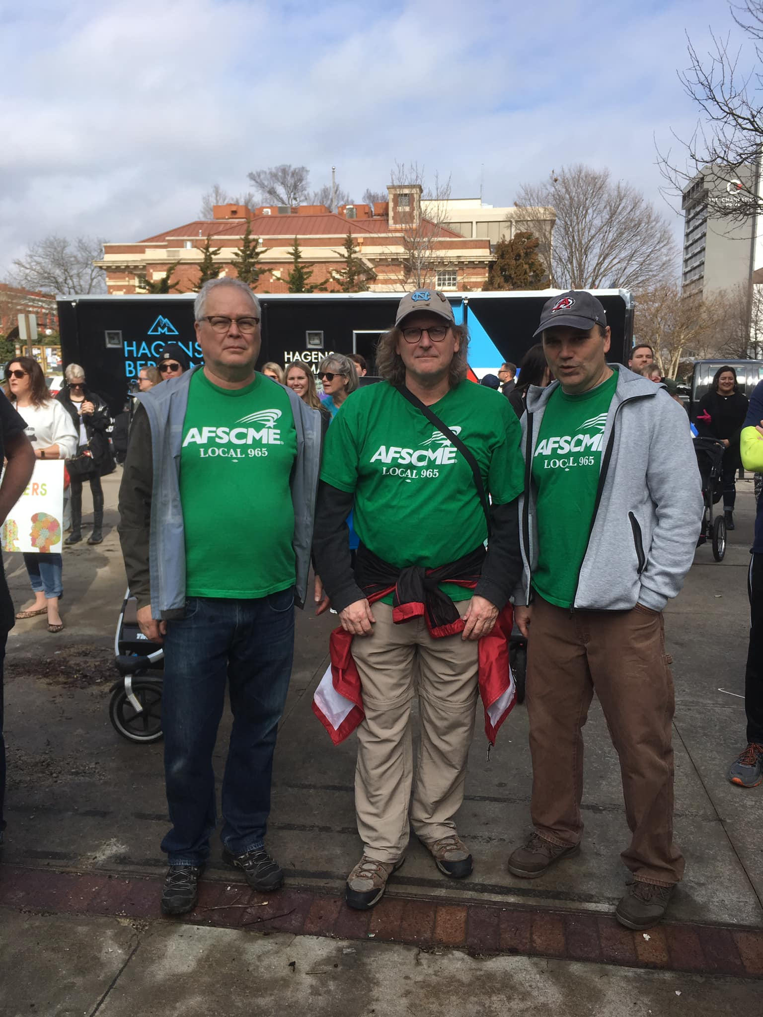 From left, Ted Swedenburg, Steve Boss and Mike Pierce listen to speakers at the rally that preceded the 2019 NWA Women's March, Feb. 2 in downtown Fayetteville.