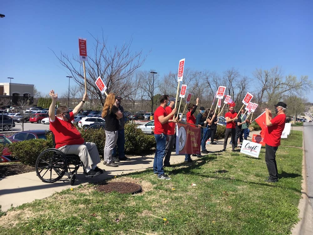 Red-shirted 965 members Hershel Hartford, Bret Schulte, Mike Pierce, Tricia Starks and Geoff Brock await Ted Swedenburg to shoot a photo at the Solidarity with Amazon Workers rally March 20, 2021, outside the Fayetteville Whole Foods Market.