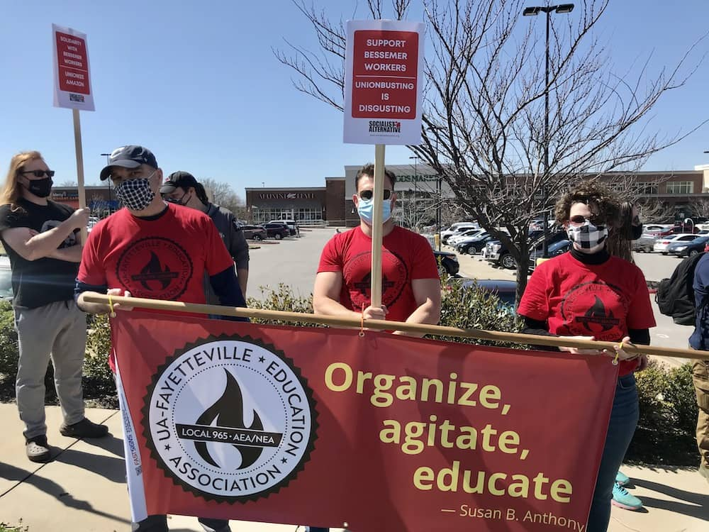 Mike Pierce, Bret Schulte and Tricia Starks hold the Local 965 banner at the Solidarity with Amazon Workers rally March 20, 2021, outside the Fayetteville Whole Foods Market.